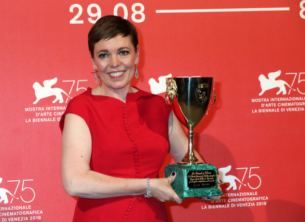 Picture shows Olivia Colman with short hair, stood in front of a red background holding her best actress trophy